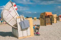De paarkou ontspant in gestreept roofed stoelen op zandig strand in Travemunde , Lübeck, Duitsland royalty-vrije stock afbeeldingen