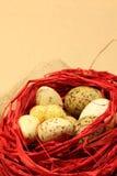 De paaseieren van kwartels In een rood nest Stock Afbeelding
