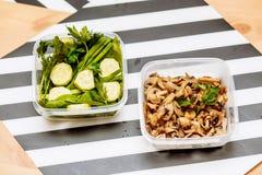 De paddestoelen, de verse kruidendille, de peterselie, de uien, spinazie en besnoeiings de stukken komkommers op twee containers  stock foto