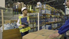 De pakhuisarbeiders controleren koopwaar stock video
