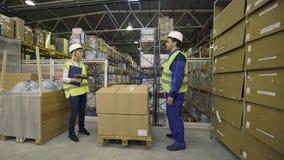 De pakhuisarbeiders controleren koopwaar stock videobeelden