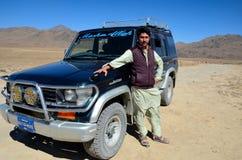 De Pakistaanse jeepbestuurder in salwar kameez stelt met jeep bij Deosai-Vlaktes Skardu Pakistan Stock Afbeelding