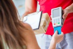 De pakketlevering die met pos en creditcard worden betaald stock afbeelding