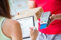 De pakketlevering die met pos en creditcard worden betaald stock foto