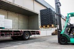 De pallet van de arbeiderslading met een vorkheftruck in een vrachtwagen Royalty-vrije Stock Fotografie