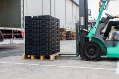 De pallet van de arbeiderslading met een vorkheftruck in een vrachtwagen Stock Foto