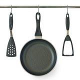 De pan en het keukengerei die van het gebraden gerecht op een spoor hangen stock afbeelding