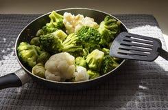 De pan met verse ontdooide groenten en keukenspatel royalty-vrije stock fotografie