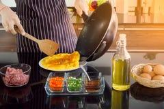 De pan van de jonge mensendraai en gebruiks houten spatel om uit omelet op de plaat weg te knippen, die ontbijt in de ochtend maa stock foto's