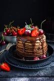 De pannekoeken van de Ombrechocolade met verse bessen en chocoladesaus royalty-vrije stock afbeeldingen