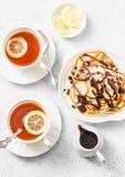 De pannekoeken van de kokosnotenbloem met banaan en chocoladesaus en thee met citroen op een lichte achtergrond, hoogste mening H Stock Foto