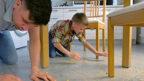 De papa berispt zijn zoon voor verspreid voedsel op de keukenvloer en maakt hem schoonmaken Maak cornflakes van de vloer schoon stock videobeelden