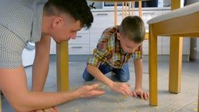 De papa berispt zijn zoon voor verspreid voedsel op de keukenvloer en maakt hem schoonmaken Maak cornflakes van de vloer schoon stock video