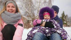 De papa duwt haar dochter op een rubber opblaasbare sneeuwbuis in langzame motie stock videobeelden