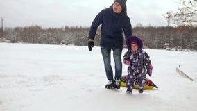 De papa duwt haar dochter op een rubber opblaasbare sneeuwbuis in langzame motie stock footage