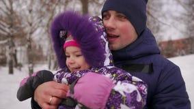 De papa duwt haar dochter op een rubber opblaasbare sneeuwbuis in langzame motie stock video
