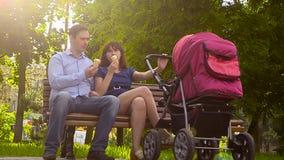 De papa en de moeder eten roomijs, gang met babywandelwagen in park, familievakantie op dag weg in de zomer stock videobeelden