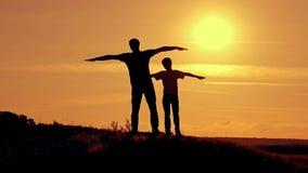 De papa en de zoon bij zonsondergang tonen de vlucht van de vliegtuigen stock video