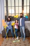 De papa en de dochter van het familiemamma met het schoonmaken van levering bij woonkamer Wij houden van netheid en netheid Samen stock foto's