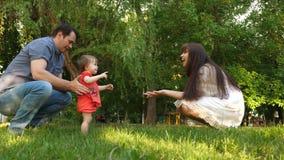 De papa en het Mamma leren om weinig dochter in park op groen gras te lopen Het mamma kust dochter op de wang en lacht met papa stock videobeelden
