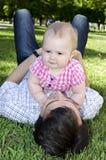 De papa en zijn dochter liggen op het gras in het park Stock Afbeelding