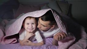De papa en zijn kleine zoon spelen het verbergen onder de deken in dark stock footage
