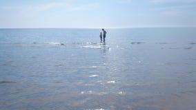 De papa en de zoon beginnen de stuk speelgoed motorboot bij het overzeese strand stock video