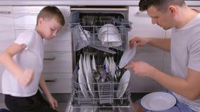 De papa en de zoon brengen schotels in afwasmachine in de keuken samen stock video