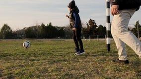 De papa en de zoon hebben pret in openlucht speelvoetbal in de lente op zonsondergang langzame motie stock video