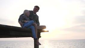 De papa en de zoon letten op de zonsondergang in het overzees stock footage