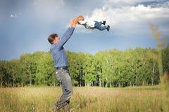 De papa en de zoon stoeien in de opheldering stock afbeeldingen