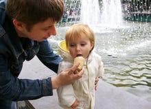 De papa geeft aan dochterroomijs Stock Foto