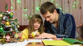 De papa helpt dochter aan het element van Kerstmis met de hand gemaakt artikel dat wordt gelijmd stock video