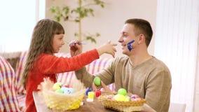 De papa houdt een borstel met verf op de neus van het meisje, en zij raakt zijn neus met een vuile hand stock footage