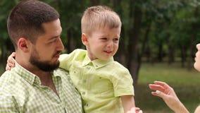 De papa houdt zijn schreeuwende zoon in zijn wapens in het Park stock video