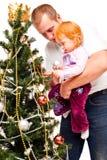 De papa met dochter verfraait een nieuw-jaarboom Stock Foto