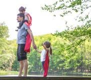 De papa met twee dochters, speelt een super held Royalty-vrije Stock Fotografie