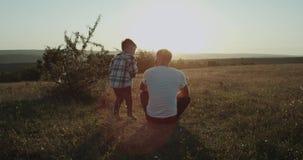 De papa met zijn zoon die bij aard een perverse mantijd doorbrengen samen, papa zit op het gras weinig jongen die uit komen stock videobeelden