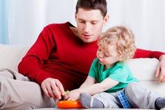 De papa met zoon zit op de laag en het spelen Royalty-vrije Stock Foto's