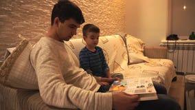 De papa met zwart haar in een witte sweater en een kleine zoon in blauw, gestreept, bekijkt de encyclopedie, zittend op zacht stock videobeelden