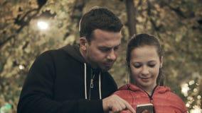De papa omvat de dochter van muziek op smartphone in hoofdtelefoons Een meisje danst in de straat luisterend aan een lied stock video