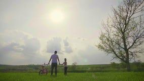 De papa onderwijst dochter hoe te om fiets op de weide in zonsondergangtijd te berijden De gelukkige vader verheugt zich dat haar stock footage