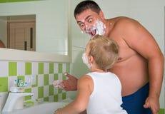 De papa onderwijst om haar te scheren weinig zoon Het kind wil als papa zijn stock afbeelding