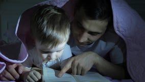 De papa onderwijst zijn kleine zoon om een boek te lezen die onder de deken verbergen stock videobeelden