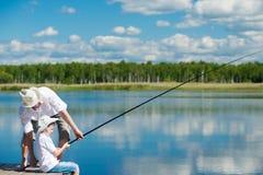 De papa onderwijst zijn zoon op de aard om te vissen Royalty-vrije Stock Fotografie