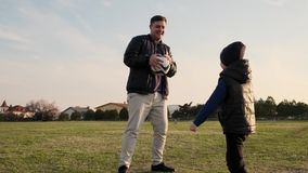 De papa piddles en plaagt met zijn zoon tijdens de langzame motie van het voetbalspel in openlucht stock footage