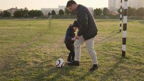 De papa piddles en plaagt met zijn zoon tijdens de langzame motie van het voetbalspel in openlucht stock video