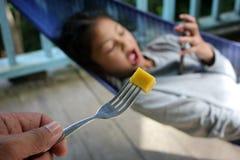 De papa voedt een mango aan zijn dochter die ` s slechts met de telefoon interesseerde royalty-vrije stock foto's