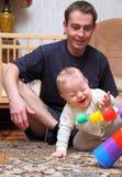 De papa ziet hoe zijn baby aan blij Stock Foto