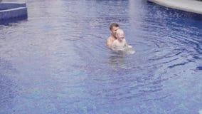 De papa zwemt in de pool met zijn zoon stock video